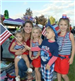 Kids and Woman Dressed in Red, White, and Blue