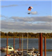 Person Flying over Water on Powered Parachute
