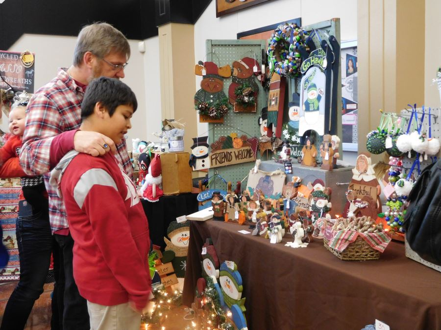 Man and Young Boy Looking at Items in Holiday Marketplace Bazaar