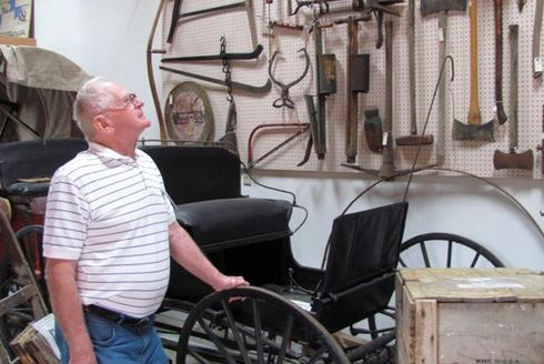 Man standing by a buggy at the Two Rivers Heritage Museum